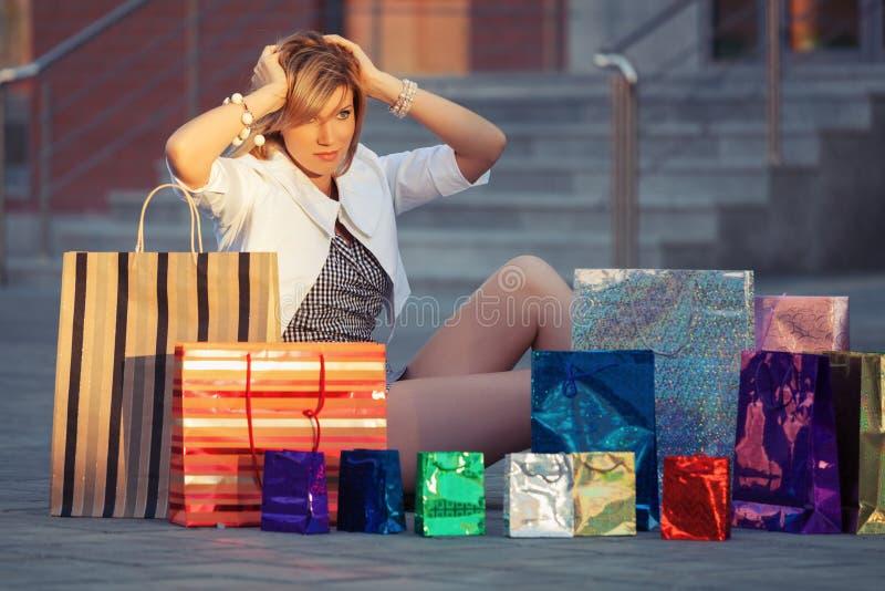 Giovane donna felice di modo con i sacchetti della spesa che si siedono sul marciapiede immagine stock libera da diritti