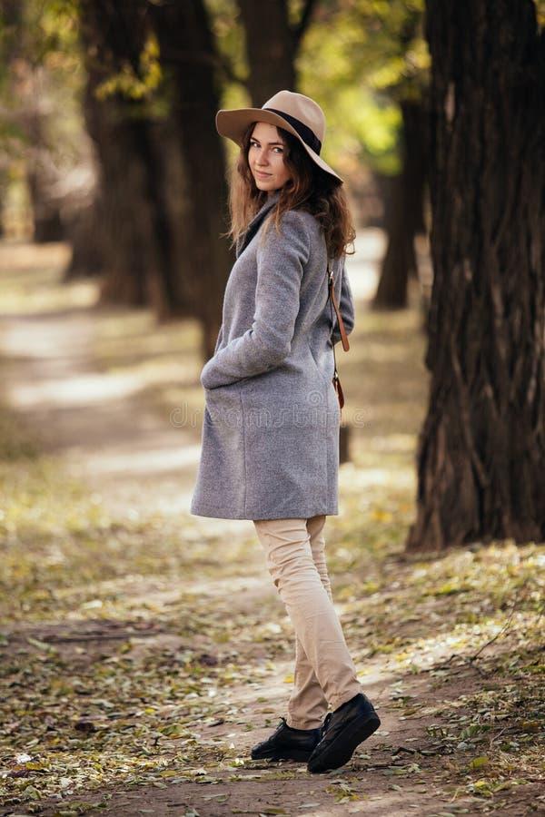 Giovane donna felice di sorriso che cammina all'aperto nel parco di autunno in cappotto e cappello Tempo soleggiato caldo Concett immagini stock libere da diritti