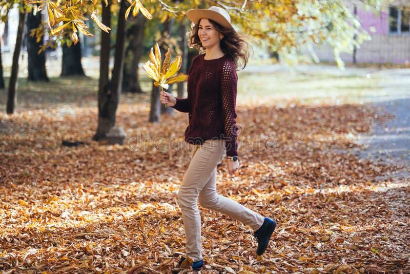 Giovane donna felice divertendosi tempo in autunno all'aperto Correre di salto sorridente allegro della ragazza nella foresta di  immagini stock