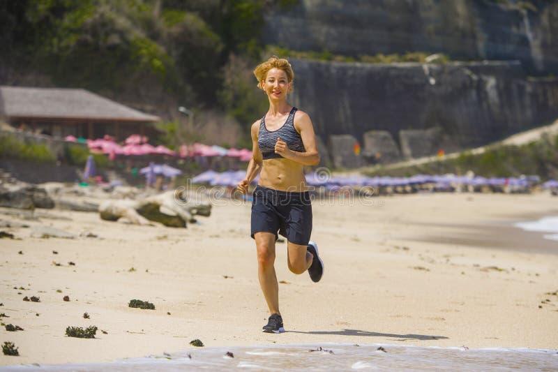 Giovane donna felice ed attraente del corridore di sport che fa allenamento corrente che pareggia sulla misura tropicale di rappr fotografie stock