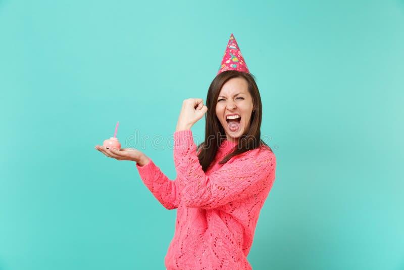 Giovane donna felice in maglione rosa tricottato, cappello di compleanno gridante facendo gesto del vincitore, tenente dolce disp fotografia stock