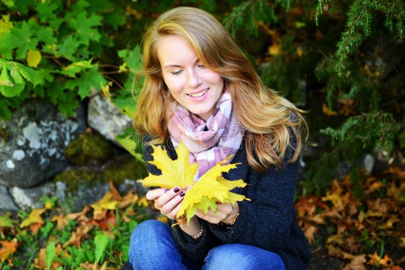 Giovane donna felice in parco il giorno soleggiato di autunno fotografia stock