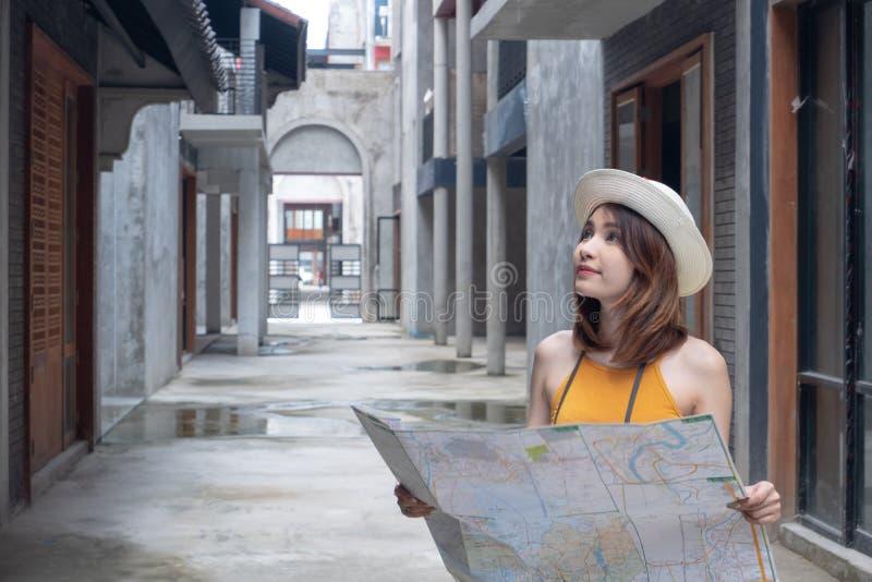Giovane donna felice persa nella mappa della tenuta della città Ragazza asiatica turistica di viaggio con la mappa Concetto di vi fotografia stock