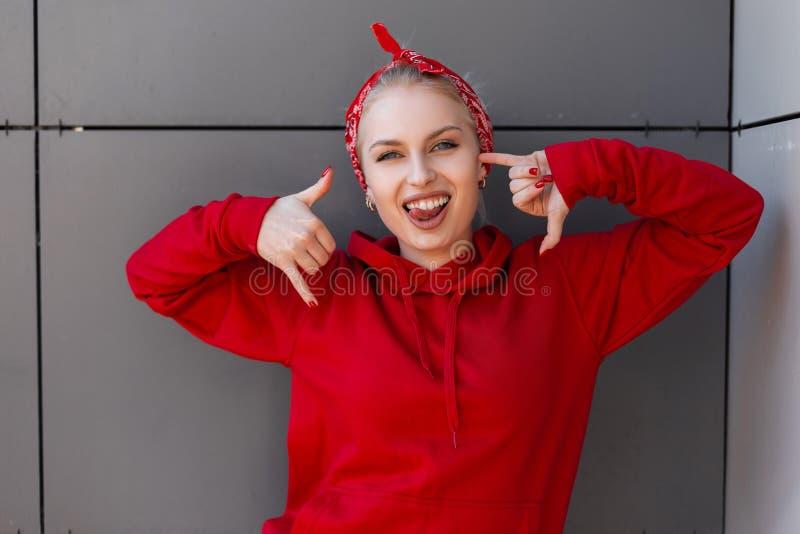 Giovane donna felice positiva con un sorriso sveglio in una maglietta felpata rossa alla moda con la bandana d'avanguardia che po immagini stock