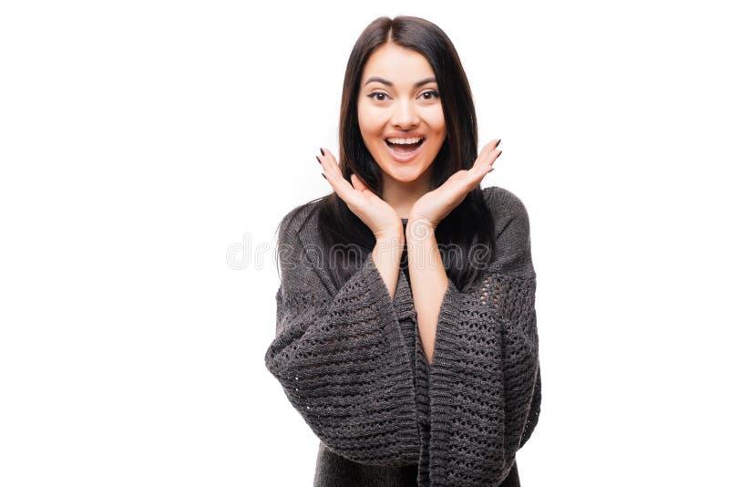 Giovane donna felice sorpresa che guarda lateralmente nell'eccitazione sopra fondo bianco fotografia stock