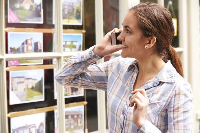 Giovane donna felice sul telefono fuori degli agenti immobiliari fotografia stock libera da diritti