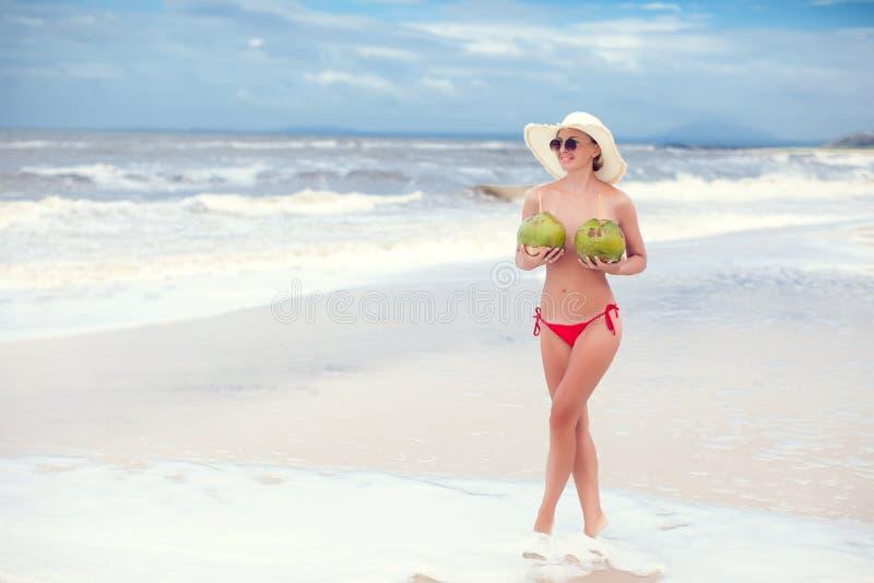 Giovane donna felice topless con le noci di cocco in mani in cappello di paglia con sulla spiaggia con una noce di cocco fotografia stock libera da diritti