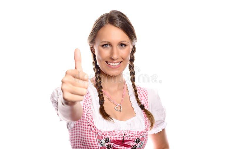 Giovane donna felice in un dare del dirndl pollici su immagini stock