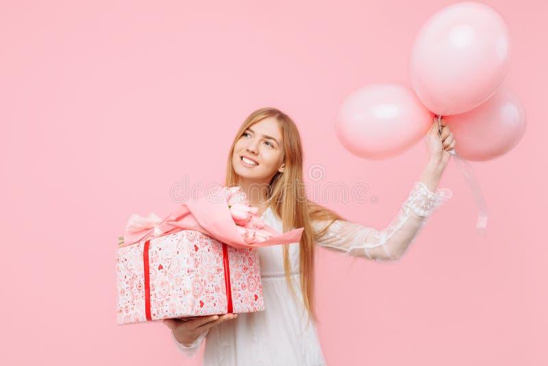 Giovane donna felice, in un vestito bianco, stante con un mazzo dei fiori, un contenitore di regalo e palloni, su un fondo rosa immagine stock