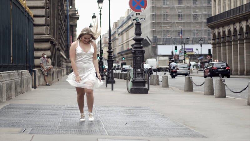 Giovane donna felice in vestito bianco che posa sulle vie della città del fondo azione Bionda attraente che sorride e che posa de immagini stock