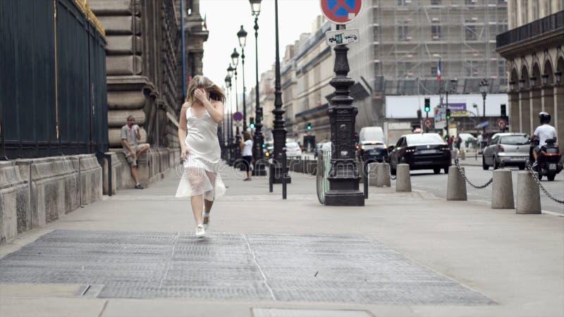 Giovane donna felice in vestito bianco che posa sulle vie della città del fondo azione Bionda attraente che sorride e che posa de fotografia stock libera da diritti
