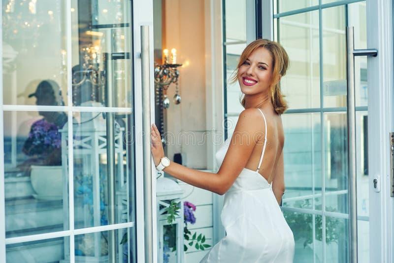 Giovane donna felice in vestito uguagliante bianco immagine stock