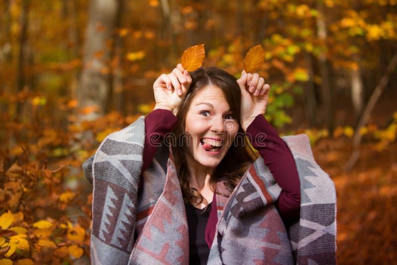 Giovane donna in foglie dell'azienda forestale a lei capa fotografie stock libere da diritti