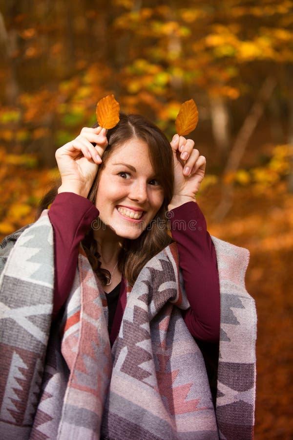 Giovane donna in foglie dell'azienda forestale a lei capa fotografia stock