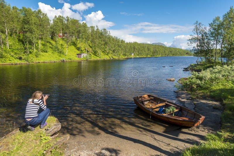 Giovane donna fotografa il lago e il paesaggio forestale nel Nordland norvegese fotografie stock libere da diritti