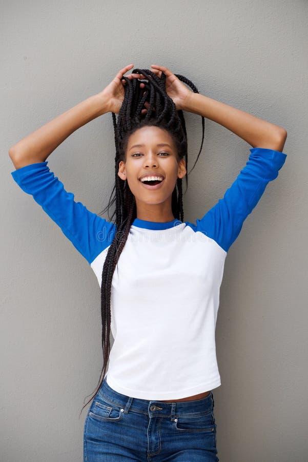 Giovane donna fresca con le mani in capelli che sorride sul fondo grigio immagine stock