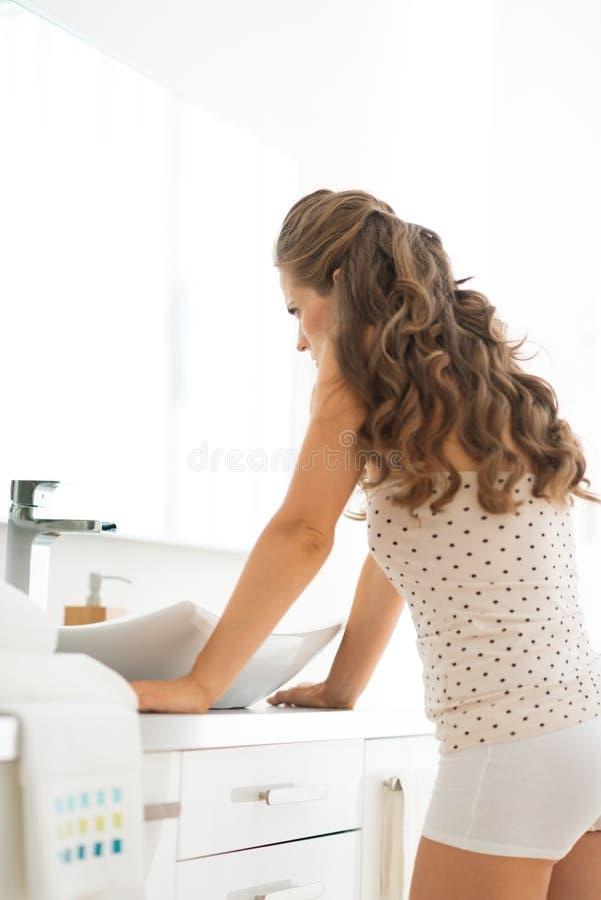 Giovane donna frustrata che sta nel bagno immagini stock