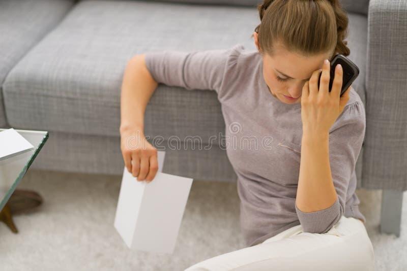 Giovane donna frustrata con la lettera ed il telefono fotografia stock libera da diritti