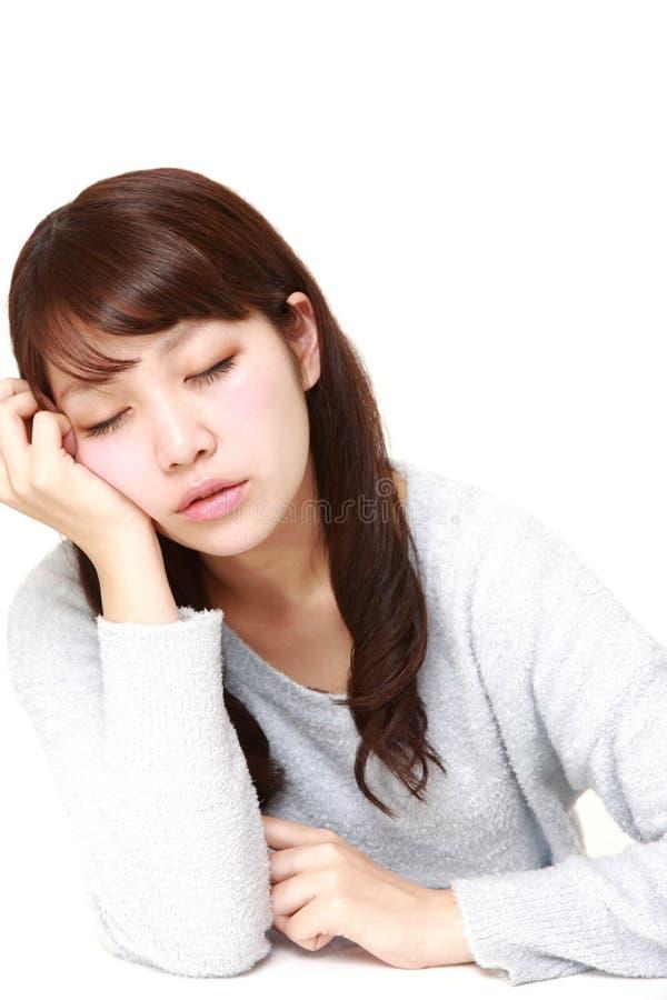 Giovane donna giapponese che dorme sulla Tabella fotografia stock