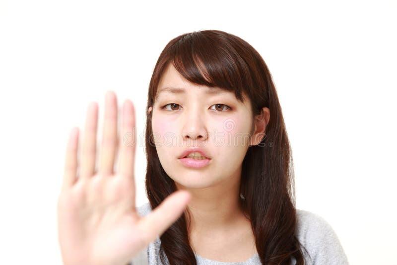 Giovane donna giapponese che fa gesto di arresto fotografia stock libera da diritti