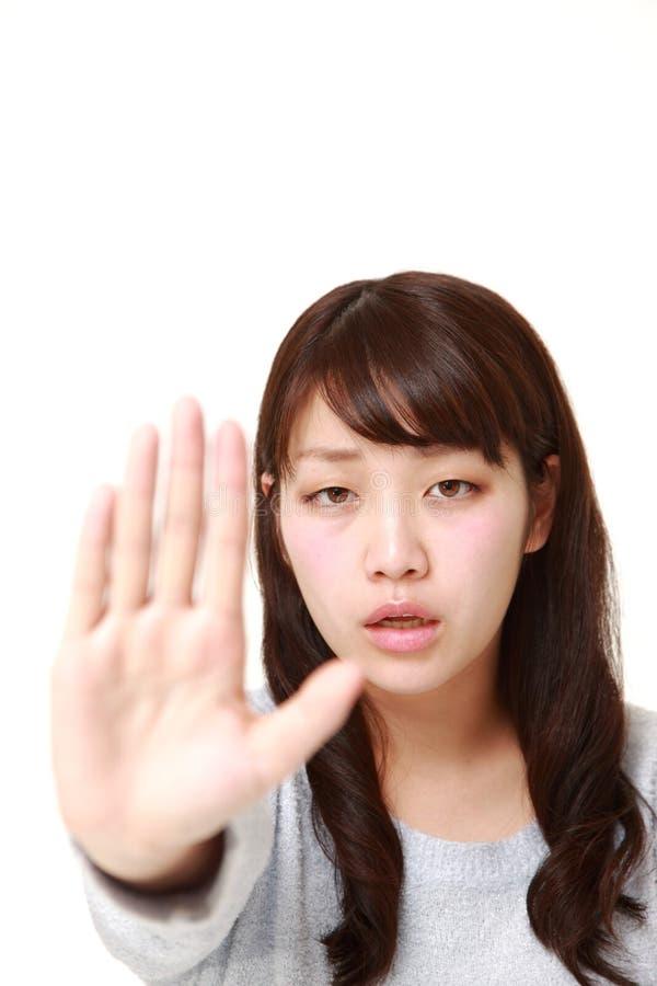 Giovane donna giapponese che fa gesto di arresto fotografie stock libere da diritti