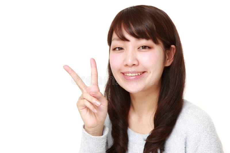 Giovane donna giapponese che mostra un segno di vittoria immagine stock