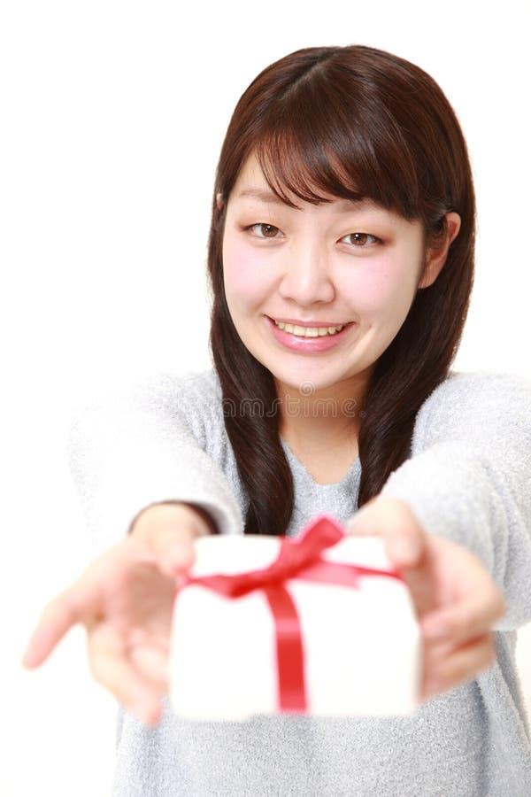 Giovane donna giapponese che offre un regalo fotografia stock libera da diritti
