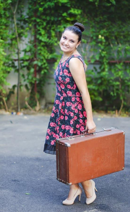 Giovane donna in gonna d'annata con e vecchia valigia immagini stock