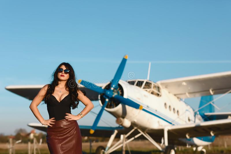 Giovane donna in gonne e vetri di cuoio vicino all'aeroplano antico Stile di vita di modo, ritratto fotografie stock