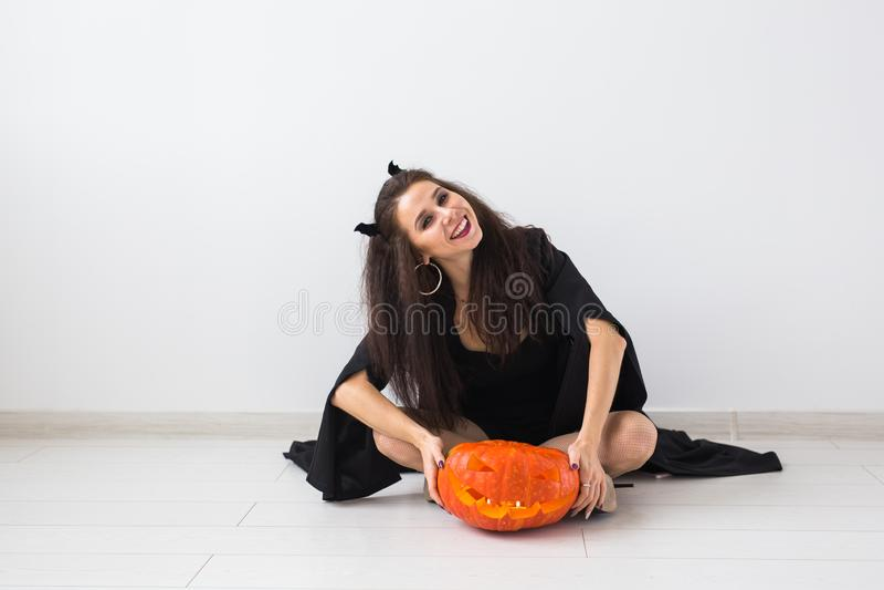 Giovane donna gotica felice in costume di Halloween della strega che sorride sopra il fondo della stanza bianca fotografia stock libera da diritti