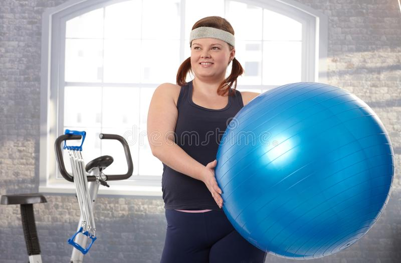 Giovane donna grassa che si esercita con la sfera di misura immagine stock libera da diritti