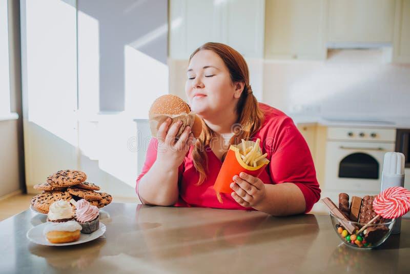 Giovane donna grassa in cucina che si siede e che mangia alimenti industriali Stile di vita non sano Tenga l'hamburger e le patat immagine stock libera da diritti