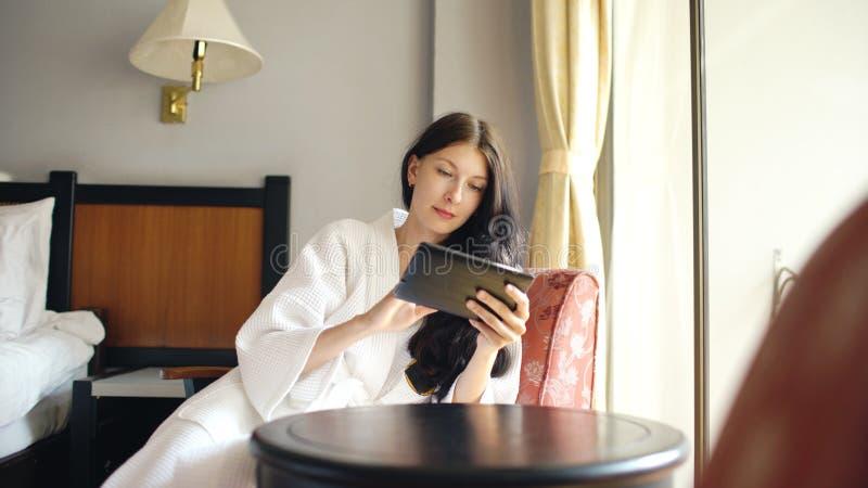 Giovane donna graziosa in accappatoio che chiacchiera sul computer della compressa che si siede sulla sedia nella camera di alber immagini stock libere da diritti