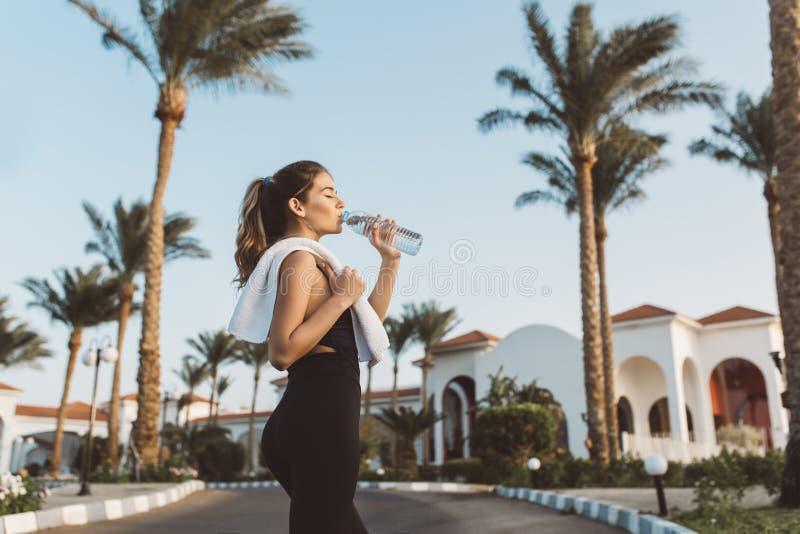Giovane donna graziosa alla moda in acqua potabile degli abiti sportivi sulla via sulle palme, fondo del cielo blu Umore allegro fotografia stock