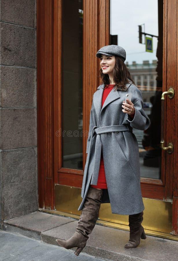 Giovane donna graziosa alla moda che porta vestito rosso, cappotto grigio e cappello posanti nelle vie della città immagine stock libera da diritti