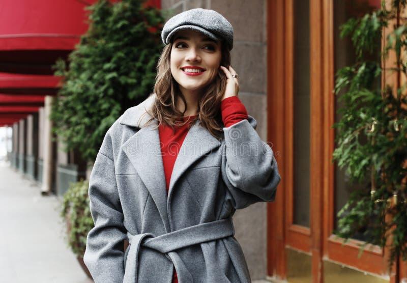 Giovane donna graziosa alla moda che porta vestito rosso, cappotto grigio e cappello posanti nelle vie della città fotografia stock