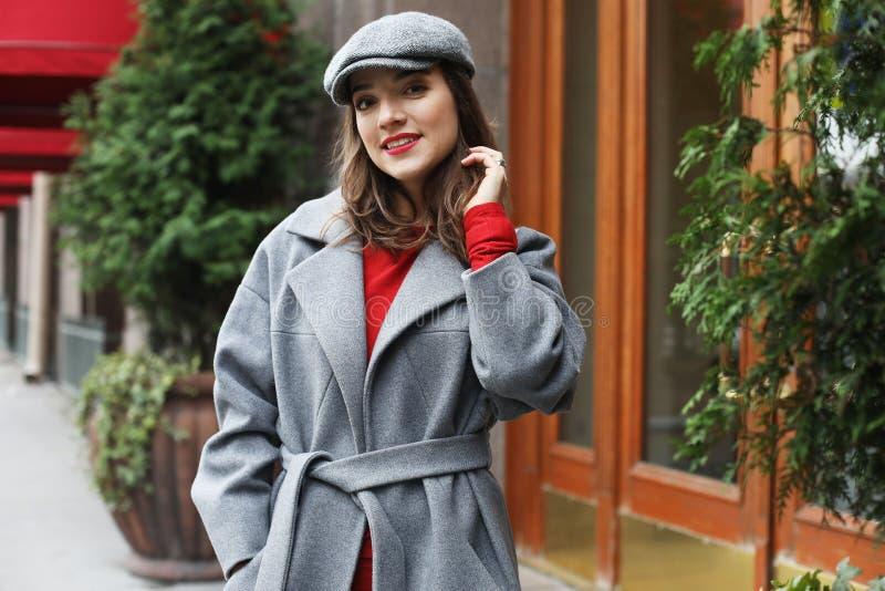 Giovane donna graziosa alla moda che porta vestito rosso, cappotto grigio e cappello posanti nelle vie della città fotografie stock libere da diritti