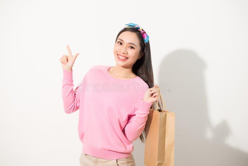 Giovane donna graziosa allegra che alza i sacchetti della spesa, dancing ed esaminante macchina fotografica Concetto di consumism fotografia stock
