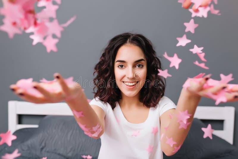 Giovane donna graziosa allegra sveglia del ritratto in pigiami con capelli castana ricci divertendosi alla macchina fotografica s fotografie stock