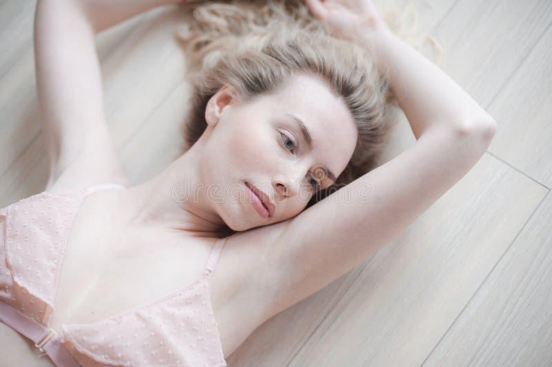 Giovane donna graziosa in biancheria delicata che si trova sul pavimento Ritratto alto vicino del fronte femminile con pelle natu immagini stock