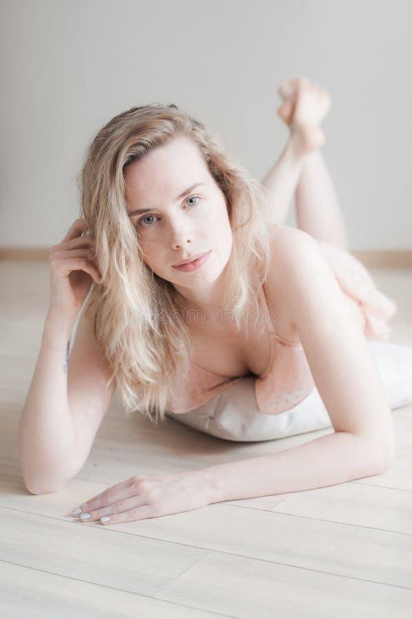Giovane donna graziosa in biancheria delicata sul pavimento, sguardo alla macchina fotografica Ritratto del fronte femminile con  fotografia stock libera da diritti