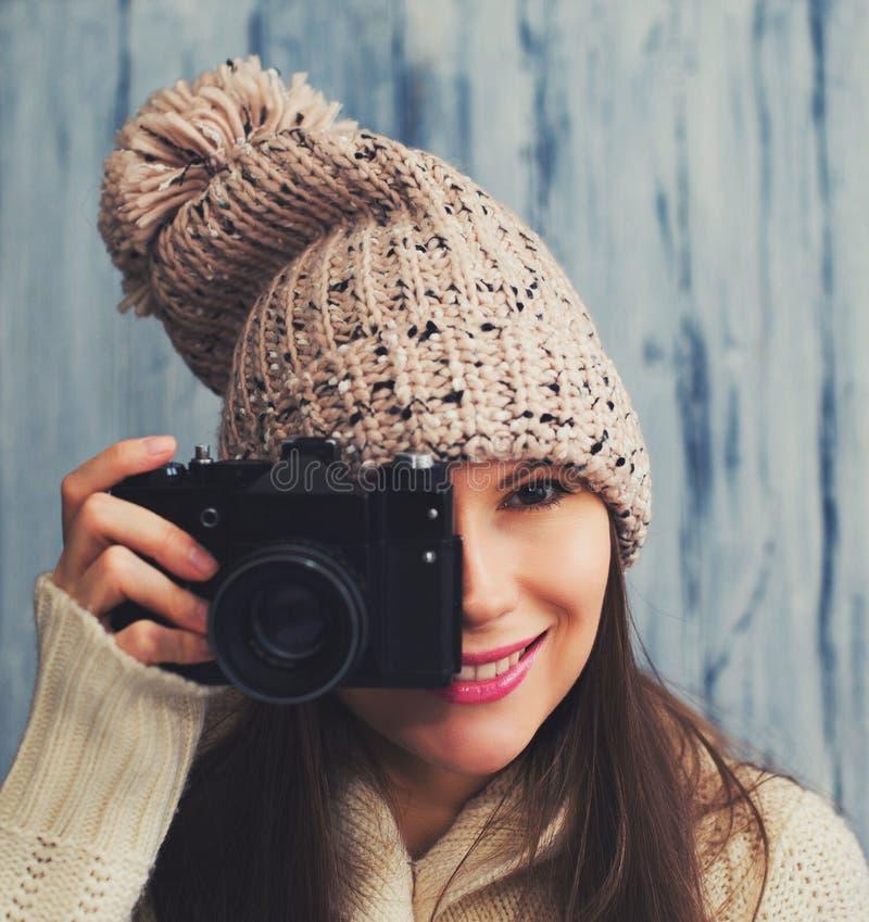 Giovane donna graziosa in cappello con la macchina fotografica d'annata fotografie stock