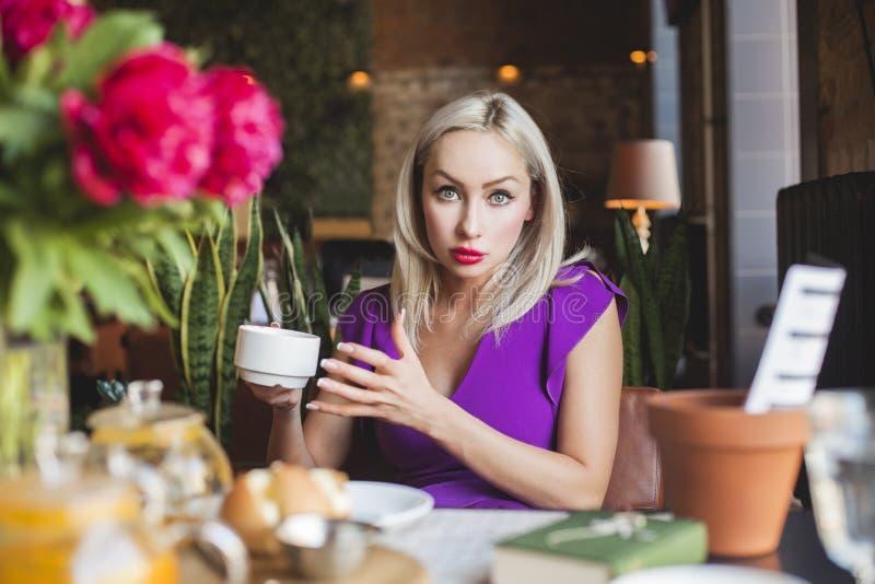 Giovane donna graziosa che chiacchiera in caffè fotografie stock