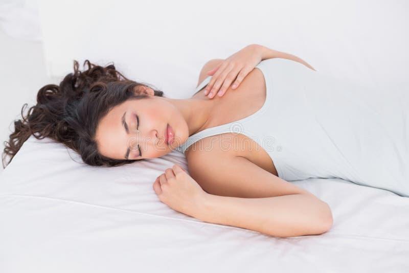Giovane donna graziosa che dorme con gli occhi chiusi a letto fotografia stock libera da diritti