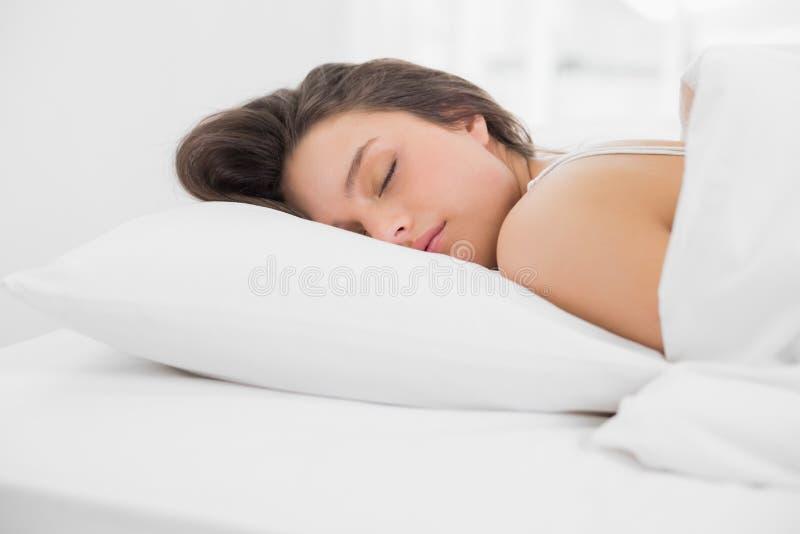 Giovane donna graziosa che dorme a letto fotografia stock