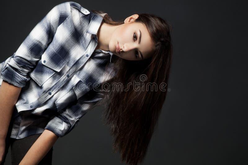 Giovane donna graziosa che esamina macchina fotografica sopra fondo grigio immagine stock libera da diritti