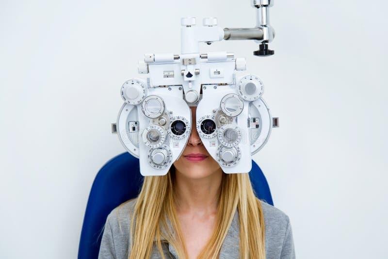 Giovane donna graziosa che fa misura di vista con phoropter ottico nella clinica di oftalmologia fotografia stock