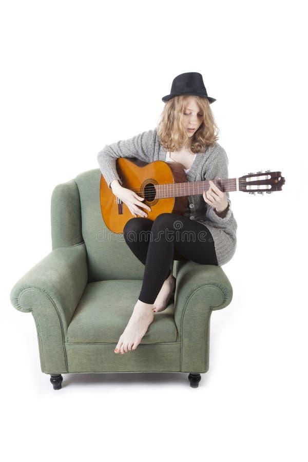 Giovane donna graziosa che gioca chitarra dal lato della poltrona immagini stock libere da diritti