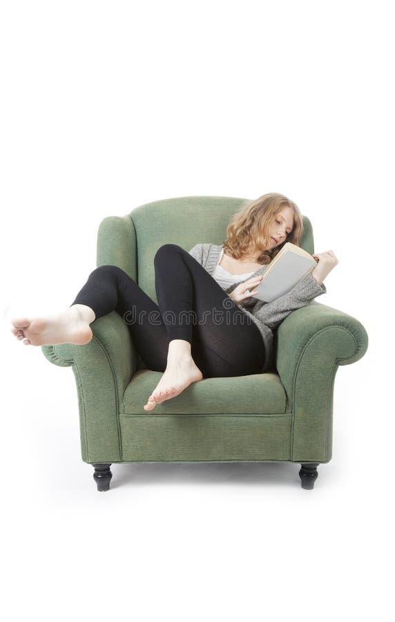 Giovane donna graziosa che legge un libro in poltrona fotografia stock