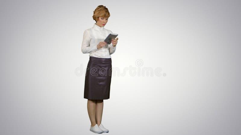 Giovane donna graziosa che per mezzo della compressa su fondo bianco fotografia stock